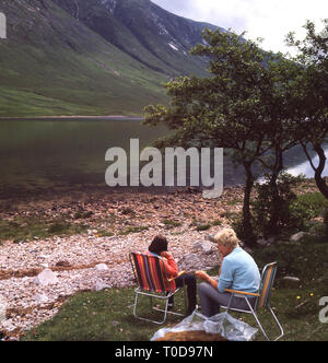 1960s, two ladies sitting in light metal camping chairs beside Loch Etive, Highlands, Scotland, - Stock Image