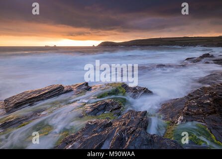 Waves rush onto the rugged shore of Booby's Bay near Trevose Head at sunset, Cornwall, England. Summer (July) 2017. - Stock Image