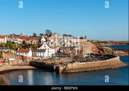 Entrance to Crail harbour and Crail in Fife Scotland viewed from west on a sunny autumn day - Stock Image