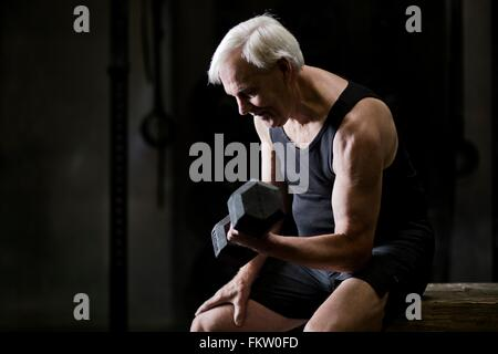 Senior man sitting doing bicep curls with dumbbell in dark gym - Stock Image