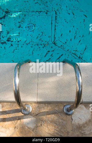 Down the stairs of a dirty pool. The stairs of swimming pool. Dirty Pool stairs. - Stock Image