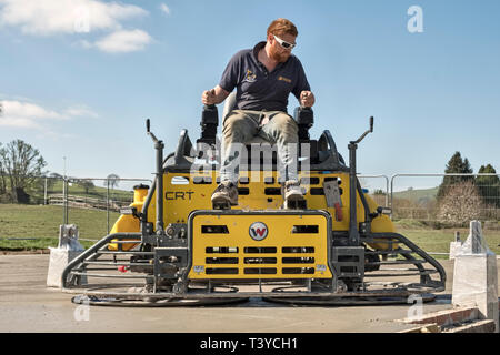 Presteigne, Powys, Wales, UK. A man using a ride-on power trowel (power float) to smooth the surface of a freshly laid concrete slab floor - Stock Image