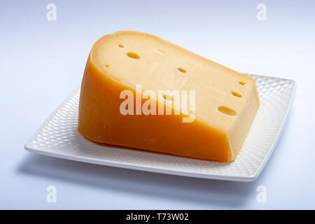 One piece of traditional Dutch  old hard cheese made from cow milk close up  on white background - Stock Image