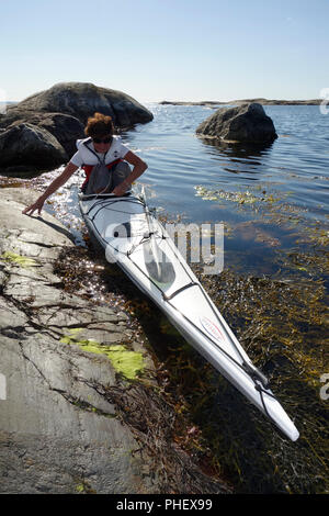 A woman keeps balance while boarding her kayak for a tour - Stock Image
