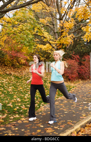 Two young women jogging together during autumn - Stock Image