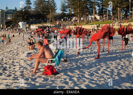Beach goers mingle with art sculptures at the 2015 Sculpture By The Sea event. Cottesloe beach, Perth. Western Australia. - Stock Image