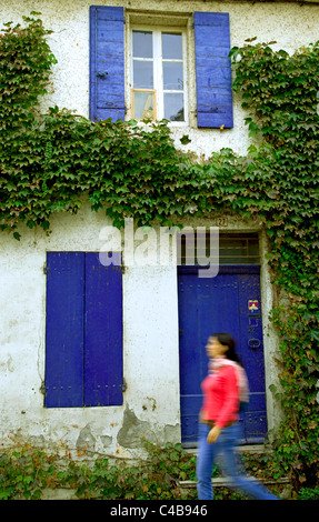 Arles; Bouches du Rhone, France; A young woman walking in front a brightly coloured house. MR. - Stock Image