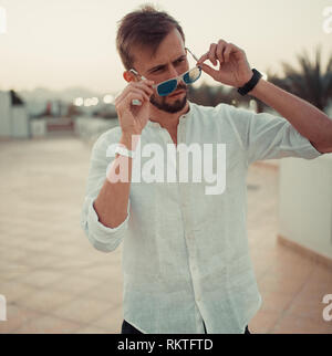 Young man stands on the roof of building in white shirt and sunglasses at sunset. - Stock Image
