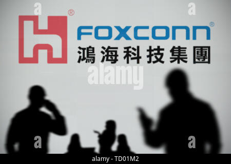 The Foxconn logo is seen on an LED screen in the background while a silhouetted person uses a smartphone in the foreground (Editorial use only) - Stock Image