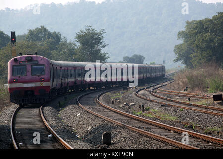 A small Indian train entering the wild forest area after departing from a station. - Stock Image