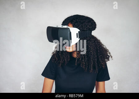 A beautiful young black woman with curly afro hair wears virtual reality VR headset and plays videogames in studio with grey background - Stock Image