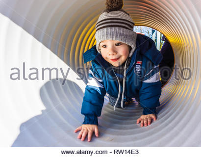 Poznan, Poland - February 16, 2019: Young toddler boy with warm winter clothes crawling in a tunnel of a climb equipment at a playground. - Stock Image