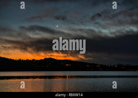 Moon sunset in cloudy sky at evening with Varese lake in the foreground and hills in the background - Stock Image