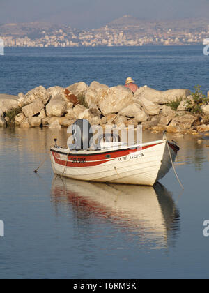 Red and white motor boat reflected in water at St. Spiridon lagoon, Corfu, Greece - Stock Image