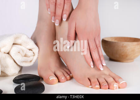 Girl legs and hands on feet with french manicure and pedicure on towel in beauty spa studio and decorative stone and bowl. Woman beauty and femininity - Stock Image