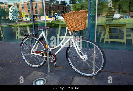 A white ladies bicycle with a Dutch style open frame rear carrier and a basket on the handle bars locked outside an Art Gallery - Stock Image