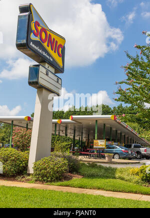NEWTON, NC, USA-9/2/18:  A Sonic drive-in fast food restaurant, showing a road sign and drive up service. 4 people visible at table under awning. - Stock Image
