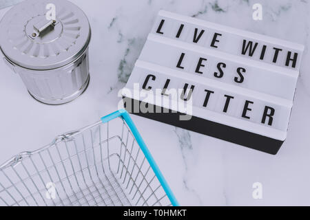ecology and consumerism concept: live with less clutter message on lightbox with shopping basket and trash bin - Stock Image