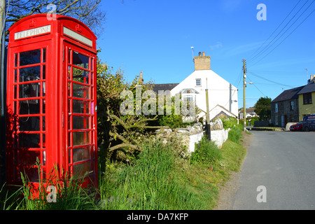 Traditional red British telephone box on a village lane. - Stock Image