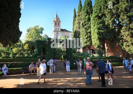 Tourists in the gardens in front of the Church of Saint Maria of Alhambra - Stock Image
