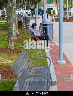 ASHEVILLE, NC, USA-4/11/19: A young woman, sitting on park bench in Pack Square, reading a book. - Stock Image