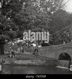 1960s, historical, a young adventure scout crosses a river on a rope bridge the scouts have recently made and tied to a tree on the riverbank, England, UK. - Stock Image