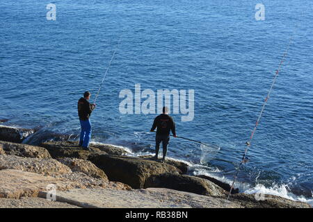 Two men fishing form the breakwater in the port of Javea, Xabia,  on the Costa Blanca, Alicante Province, Comunidad Valencia, Spain - Stock Image