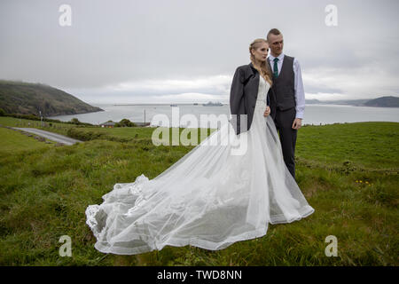 Cold bride wears the grooms jacket at her Wedding, Jennycliff, Plymouth, Devon, UK - Stock Image