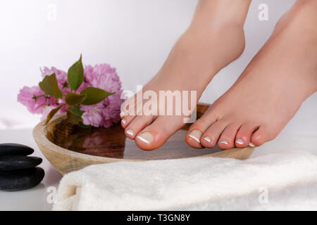 Woman feet with white french manicure on wooden bowl with pink decorative flower and towel in beauty and spa studio. Pedicure and feet health concept - Stock Image
