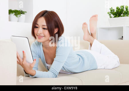 Young woman lying on sofa and using note pad with smile, - Stock Image