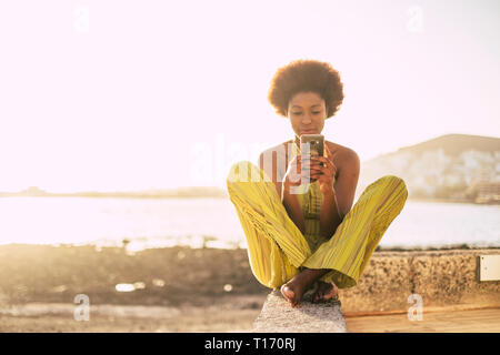 Millennial attractive alternative diversity black afro race and african hair style girl use modern cellular phone outdoor at the beach with yellow tra - Stock Image