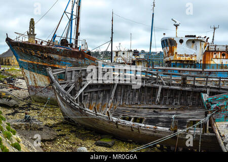 Crumbling ships with flaking paint and rotting structures in the boat graveyard at Camaret-sur-Mer in the Finistere region of Brittany, France. - Stock Image