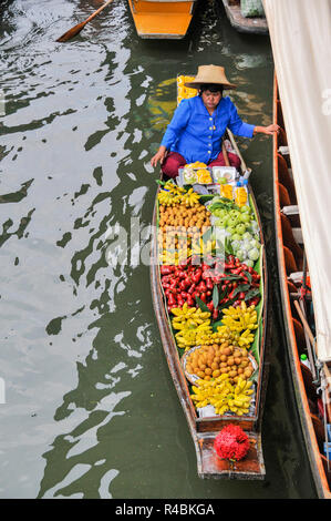 A longtail boat laden with fruit and vegetables at a floating market on a river in Bangkok Thailand - Stock Image