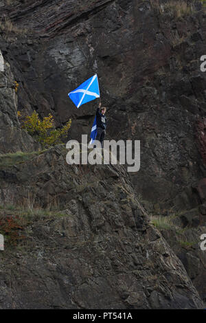 Edinburgh, UK. 6th, October, 2018. Edinburgh, Scotland, UK, Europe. A man stands alone on top of a rock at Arthur's seat waving a Scottish flag where over 100,000 people were estimated to be marching below in support for a second independence referendum. - Stock Image
