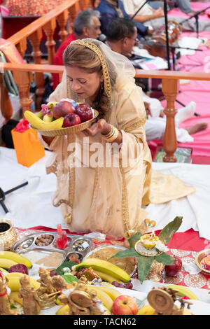 A devout Hindu worshipper making an offering to the deities at a temple in Jamaica, Queens, New York - Stock Image