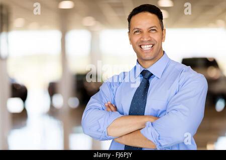 good looking male car dealer principal inside showroom - Stock Image