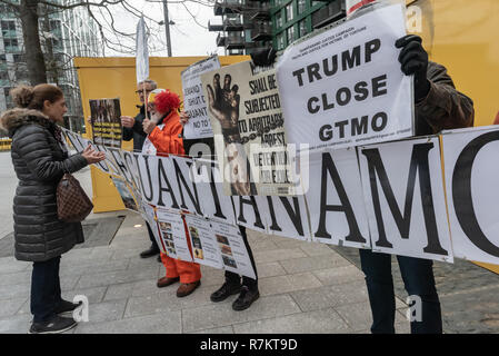 London, UK. 10th December 2018. A woman talks with protesters with  posters opposite the US Embassy at the final 'Shut Guantanamo!' monthly protest of 2018 at the US Embassy on the 70th anniversary of the Universal Declaration of Human Rights (UDHR). This declared 'No one shall be subjected to torture or to cruel, inhuman or degrading treatment or punishment' and 'No one shall be subjected to arbitrary arrest, detention or exile.' Guantanamo still has 40 detainees who have been tortured and held in indefinite detention without trial for almost 17 years. Credit: Peter Marshall/Alamy Live News - Stock Image