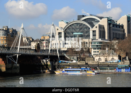 Tour boat on River Thames Charing Cross Station and Jubilee Bridge - Stock Image