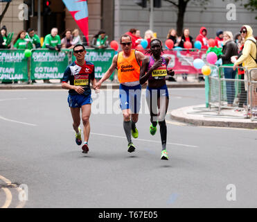 Elite Female Athlete, Linet Masai (KEN), running past Nicholas Bompard (FRA) and his guide runner, during the 2019 London Marathon. Linet finished 11th in a time of 02:26:06. Nicholas was 17th in the T11/12 Category in a time of 02:46:11 - Stock Image