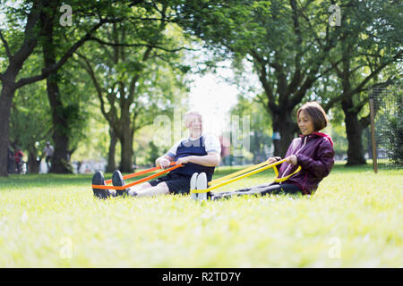 Active senior couple exercising, using resistance bands in park - Stock Image