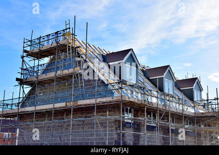 New build construction of apartments with inner skin of concrete blocks and dormer windows, England - Stock Image