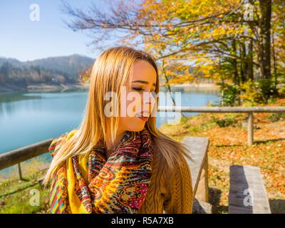 Young woman teen girl female adolescent and warm Autumn colors in nature portrait head and shoulders looking aside away sad - Stock Image