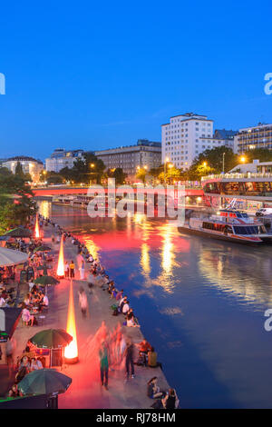 Donaukanal (Danube Canal) boat station Wien City, excursion boats, ship - restaurant' Motto am Fluss'Shore restaurants, people sitting on seawall, Wie - Stock Image