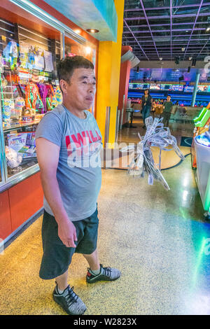 A middle-aged Asian male, dressed in shorts and t-shirt, stands in a childrens arcade with a fist full of winning tickets as he looks over the prizes - Stock Image