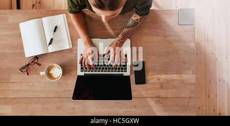Top view of woman hands typing on laptop. Female sitting at cafe table with laptop, mobile phone, diary, coffee - Stock Image