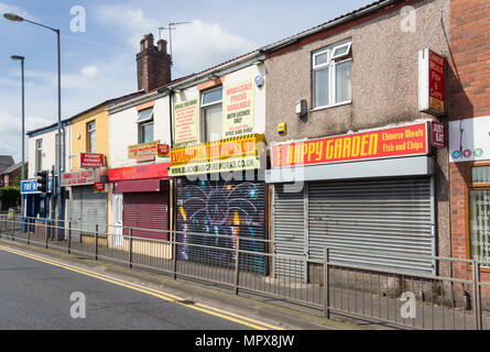 Row of shuttered shops in Albert Road, Farnworth. Three of the shops are takaway food outlets (Chinese, Indian and Pizza takeaways). - Stock Image