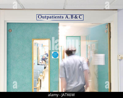 Outpatients clinic in a busy UK NHS hospital as doctor opens door is blurred in movement - Stock Image