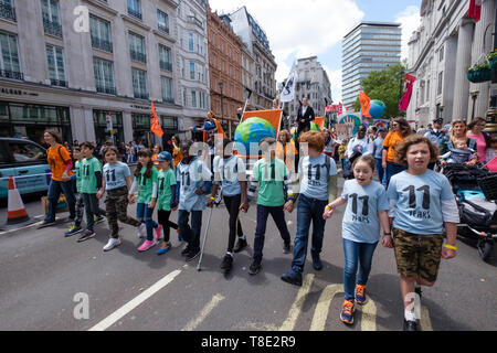 London, UK. 12th May 2019. 11-year-olds  hold hands in a line and lead several thousand mothers and children and some fathers from Hyde Park Corner to a rally filling Parliament Square, backing Extinction Rebellion's call for the drastic and urgent action needed to avert the worst consequences of climate change, including possible human extinction. Our politicians have declared a climate emergency but now need to take real action rather than continuing business as usual which is destroying life on our planet. Peter Marshall/Alamy Live News - Stock Image