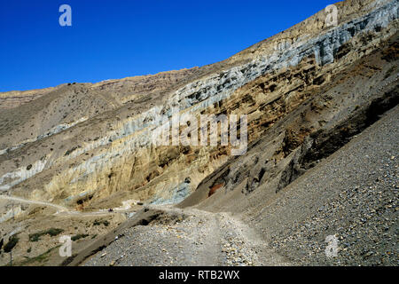 A motorcycle and its rider are dwarfed by the gigantic cliffs near Chuksang, Upper Mustang region, Nepal. - Stock Image