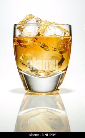 A low ball glass with whiskey and ice cubes. - Stock Image